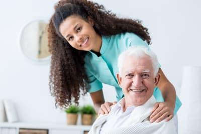 senior man and caregiver smiling
